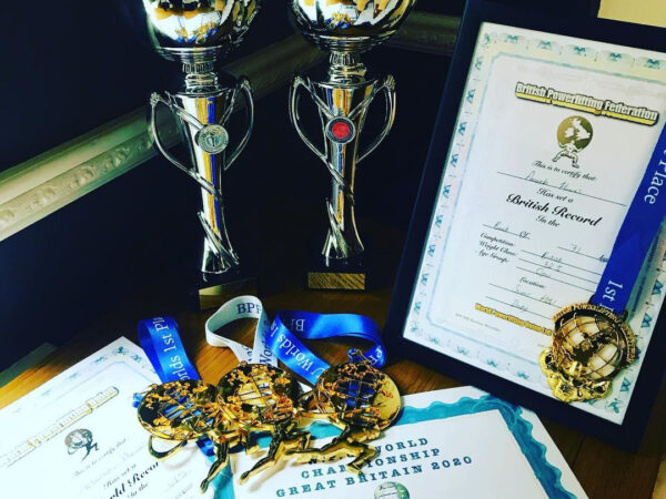 Image shows trophies, certificates and medals for powerlifting including a world record and british world record